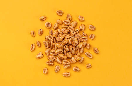 Puffed wheat cereal isolated on yellow background, top view