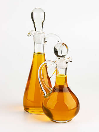 Glass decanter with olive oil on white background