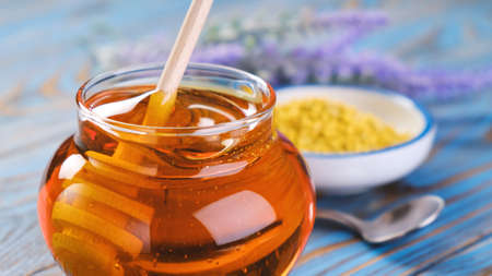 Honey in glass jar with honey dipper over wooden background