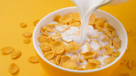 Milk pouring into bowl of corn flakes
