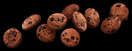 Chocolate chip cookies falling over black background