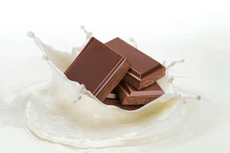 Pieces of chocolate falling into splashing milk on white background Stock fotó