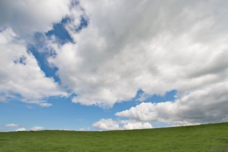 ambiente: Green field and the blue sky with clouds
