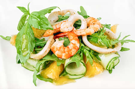 Organic seafood green salad with shrimps, squid rings, cucumber and arugula decorated with basil leaves