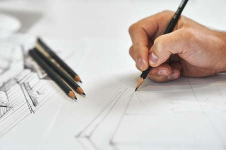 Graphic designer and artist drawing architectural blueprint with his right hand, several black pencils in background on white white sheet of paper Foto de archivo