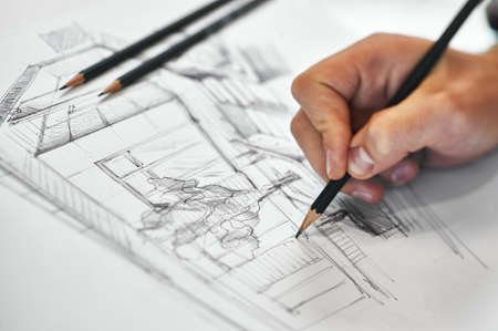 Graphic designer and artist drawing architectural blueprint with his right hand, several black pencils in background on white white sheet of paper