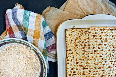 Religious Jewish kosher baked homemade bread matzo on tray decorated with cloth napkin on wooden table top view