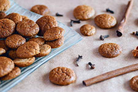 Prepared traditional seasonal round ginger cookies with cloves and cinnamon spices on plate and cooking paper