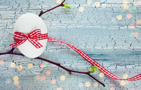 arbol de pascua: Easter holiday background with white egg, ribbon, spring branch on wooden table, blurred light effect Foto de archivo
