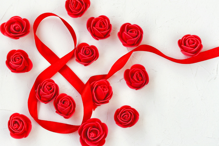 International Womens Day, 8 march composition with many red roses, silk tape, on a white textured background Stock Photo