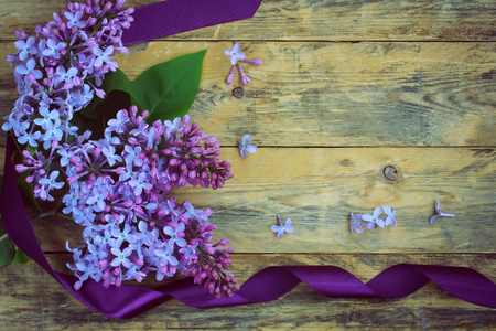 bouquet of lilac branches with purple silk ribbon on old wooden table