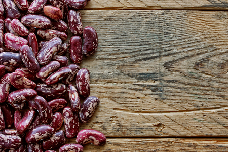 durty: Red spotted beans seeds on an old wooden table Stock Photo