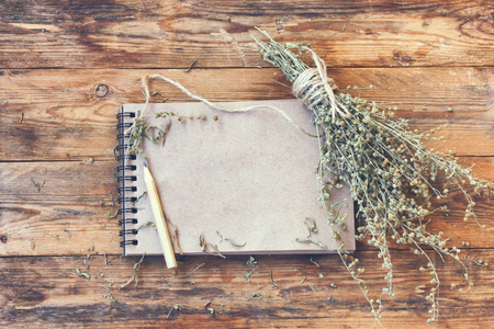 乾燥ハーブよもぎ、木製のテーブル、素朴なスタイルは、鉛筆を書くためのメモ用紙の束