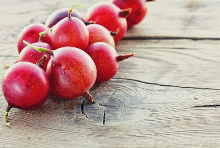 Red gooseberries on a wooden table