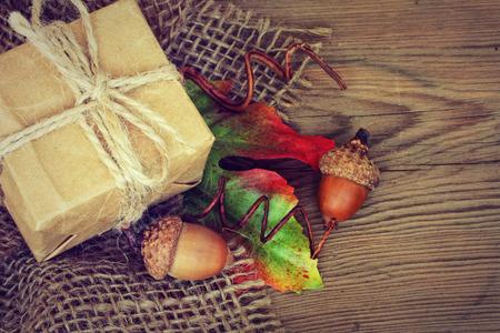 Podzimní pozadí s malou dárkovou krabičku a žaludy Reklamní fotografie