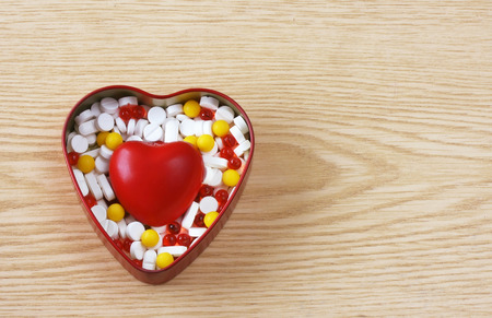 box of pills and red heart on wooden table Stock Photo