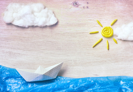 Applique with paper boat, floats in sea, plasticine sun, clouds, travel concept Stock Photo