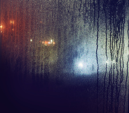 misted night window, city lights blurred