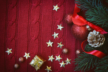 pinecones: Christmas red knitted background with branch fir, golden stars, new year ball on ribbon, gift, pine cone