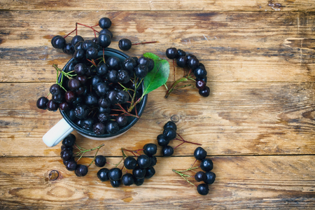bunches of chokeberry in cup,  on wooden table, prepared for jam making, rustic style, top view