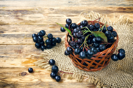 bunches of chokeberry in wicker basket, burlap cloth on wooden table, ready for cooking, rustic style Stock Photo