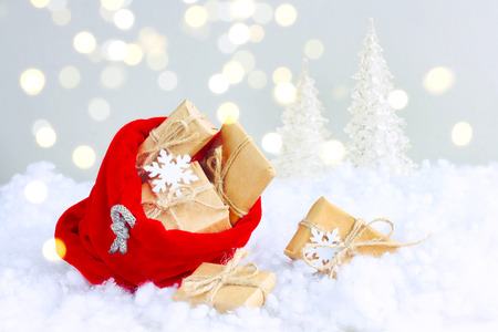 Red christmas bag with gift box lies in snow, light blur effect, new year card