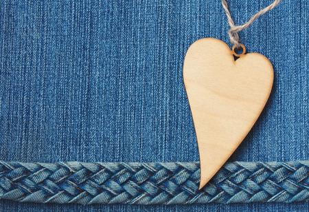 blue denim textural background, jeans braided belt, wooden heart, vintage style 免版税图像