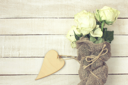 bouquet of white withered roses wrapped in burlap, plywood heart on a wooden table, vintage style