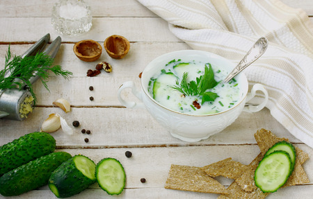 cold kefir soup with cucumber, herbs and garlic in white bowl on wooden table, summer dish Фото со стока