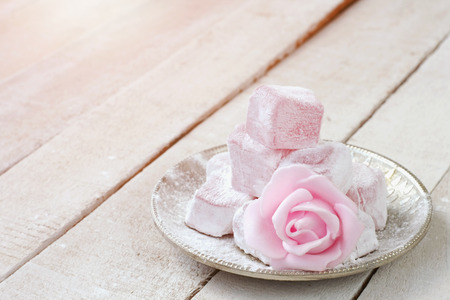 Turkish delight with rose flavor in  metal plate, pink rose flower on wooden table, closeup