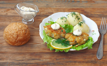 homemade fish cutlets with potatoes, dill, parsley, lettuce and lemon in white plate on wooden table, bun, tartar sauce Banco de Imagens