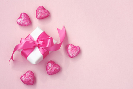 wrapped gift box with pink bow, shiny heart on paper texture background, valentines day concept