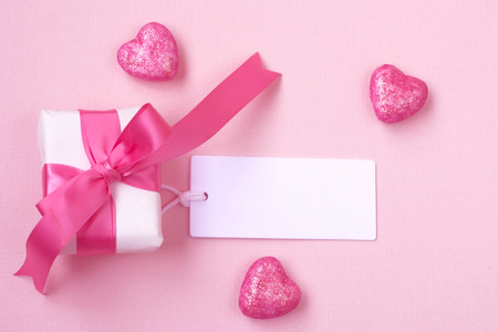 wrapped gift box with pink bow, blank tag and glitter hearts on paper texture background
