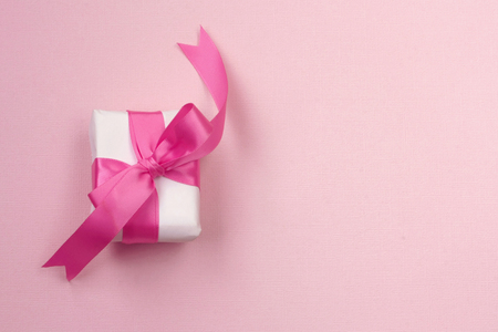 wrapped gift box with pink silk bow, on paper texture background