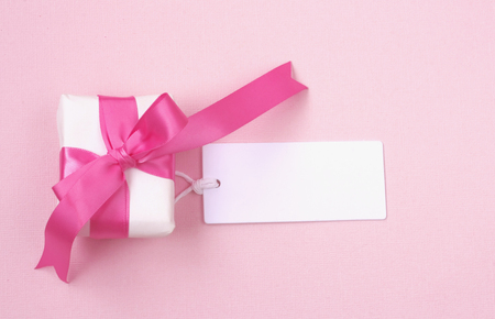 wrapped gift box with pink bow, blank tag on paper texture background