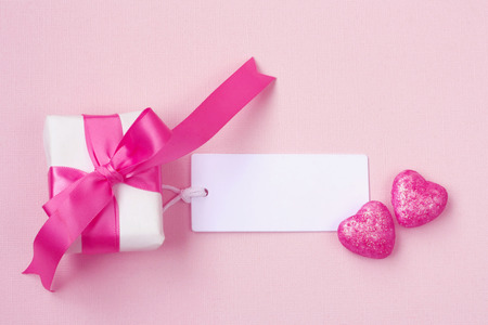 wrapped gift box with pink bow, blank tag and two hearts on paper texture background