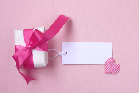 wrapped gift box with pink bow, blank tag and heart on paper texture background Banco de Imagens