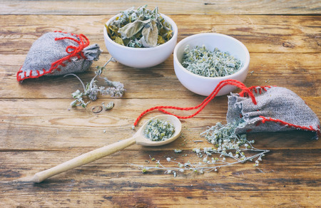 homemade sachets with wormwood, two white bowls with dry herbs, on wooden table closeup