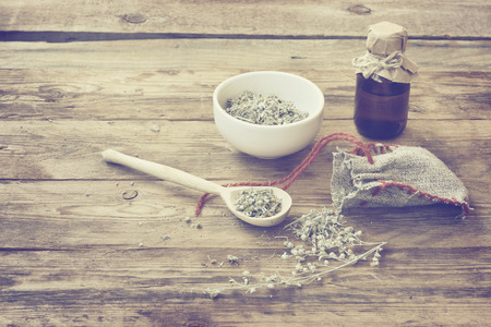 homemade sachet with wormwood, white bowl with dry herb, bottle of oil on wooden table, monochrome sepia photo, vintage style Banco de Imagens
