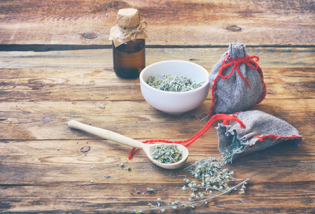 homemade sachets with wormwood, white bowl with dry herb, bottle of oil on wooden table closeup Banco de Imagens