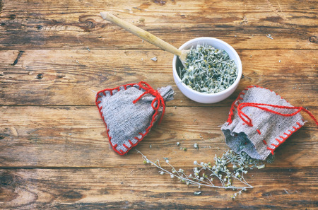 homemade sachets with wormwood, white bowl with dry herbs on wooden table, top view Banco de Imagens