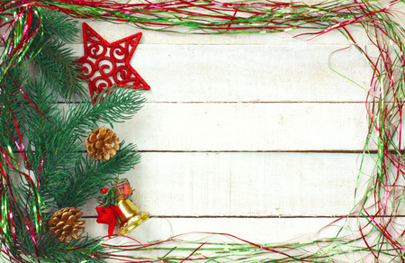 New Year Christmas background, sparkles tinsel, red carved star, decoration bell on white wooden table, space for text Banco de Imagens