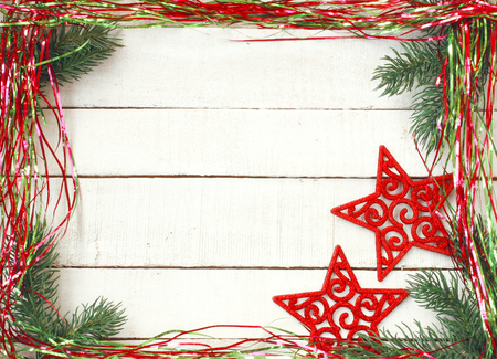 new year christmas background, shiny tinsel, red carved star, on white wooden table, space for text