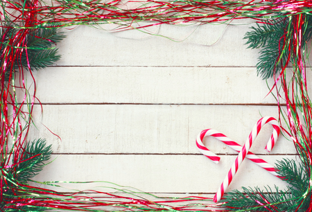 New Year, Christmas background, tinsel, candy striped, branches of fir-tree on white wooden table Banco de Imagens