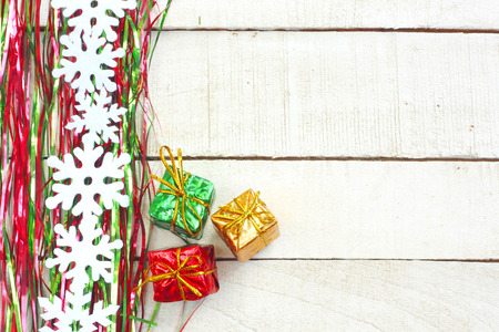 New Year, Christmas background, green and red tinsel, garland snowflakes, three gift boxes on white wooden table Banco de Imagens