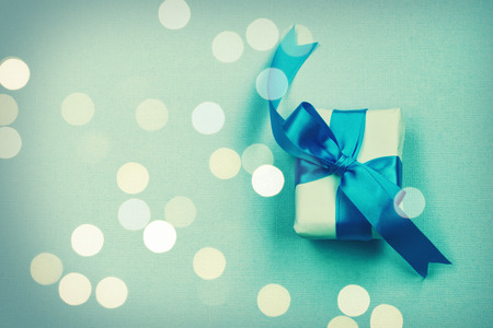 wrapped gift box with silk bow, on paper texture background, holiday birthday, father day concept, defocused light Banco de Imagens