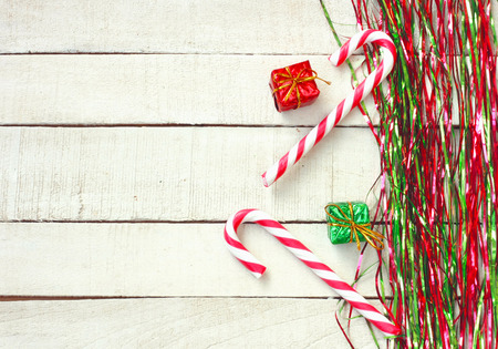 New Year, Christmas background, green and red tinsel, striped lollipop, gift box on white wooden table