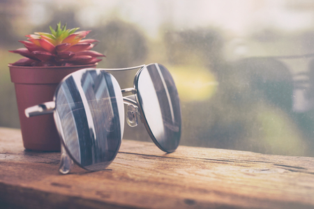 mirror sunglasses, city reflection, pot with succulent near the window on wooden table, retro style background