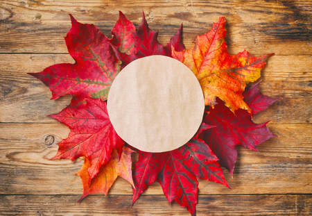 autumnal background, red maple leaves, blank paper circle for text, on wooden table, top view, flat lay
