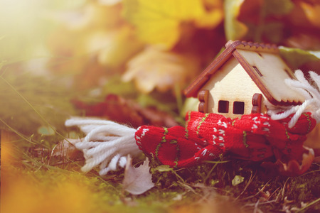little toy house wrapped scarf in autumn forest, illuminated by sun, close-up photo, selective focus Banco de Imagens